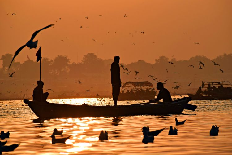 Fishers in small fishing boat on the water at sunset