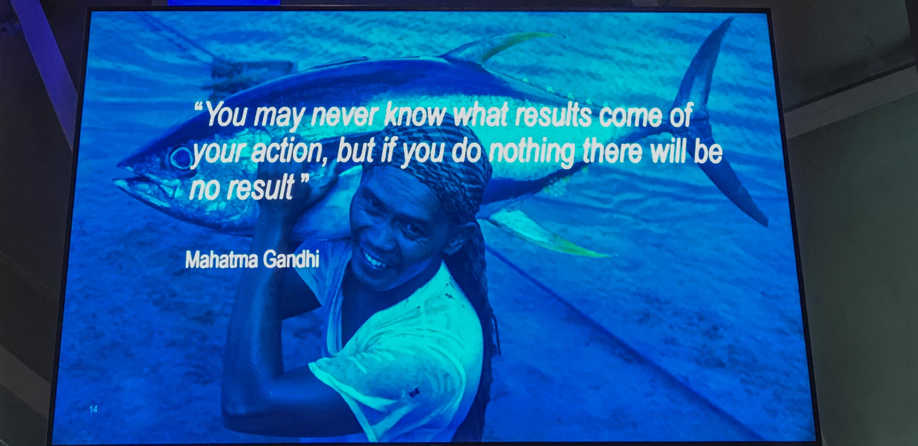 """Slide from WWF presentation at 2019 World Seafood Expo Brussels with image of a person carrying a fish and quote """"You may never know what results come of your action, but if you do nothing there will be no result"""" - Mahatma Gandhi"""