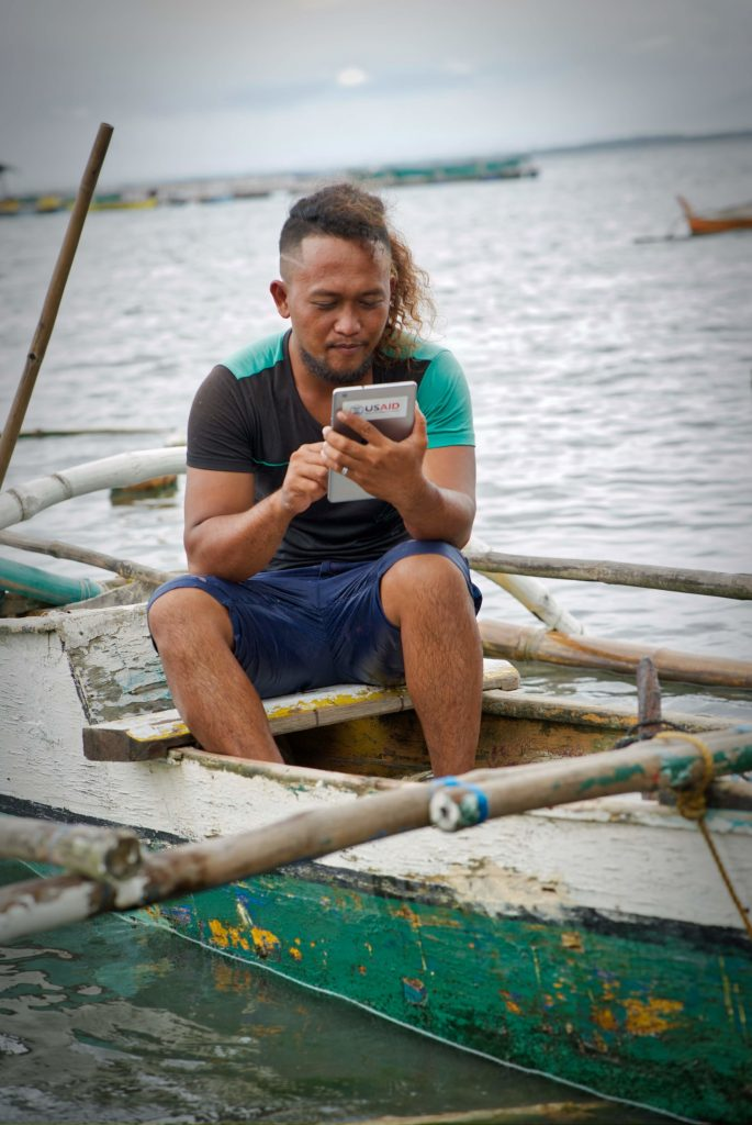 A man on a boat using an iPad with USAID sticker on the back