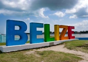 Belize sign with water and cloudy sky in the background