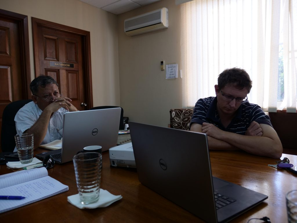 Lobster fishery staff sit at a desk with their computers during a Skype interview.