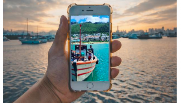 Screenshot of title and holding a phone with an image showing a fishing boat